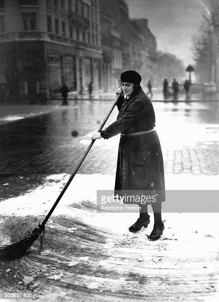 Employee de la voirie balayant la neige tombee pendant la nuit a Paris France le 1er fevrier 1930