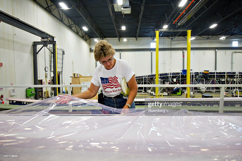 Employee Diane Hovenga secures plastic over the fiberglass fabric used to make a structural support for a wind turbine blade for General Electric Co.'s renewable energy business at TPI Composites Inc.'s manufacturing facility in Newton, Iowa, U.S., on Friday, June 22, 2012. The U.S. Census Bureau is scheduled to release durable goods data on June 27. Photographer: Daniel Acker/Bloomberg via Getty Images