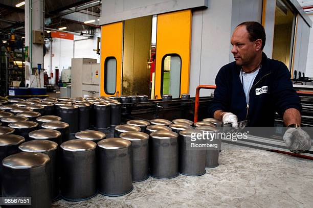 Employee Diego Savadori checks oil filter canisters at the Tecnocar car parts factory operated by Sogefi SpA near Turin Italy on Monday April 19 2010...
