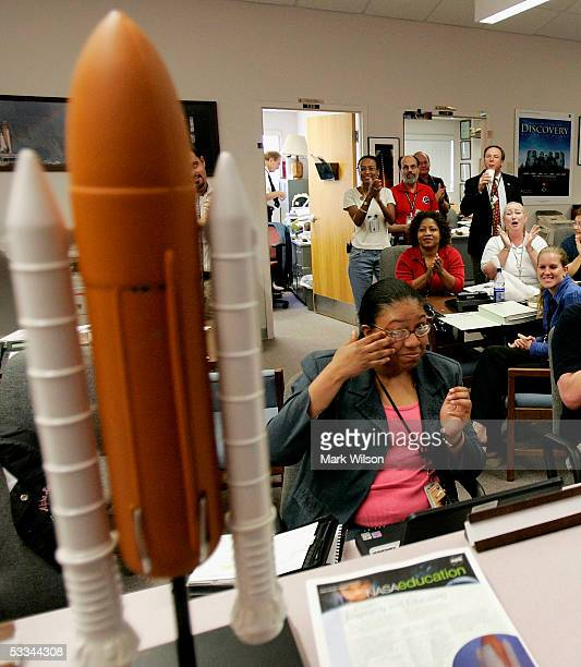 NASA employee Dolores Beasley wipes her eye while celebrating space shuttle Discovery's landing at Edwards Air Force Base at the Kennedy Space Center...
