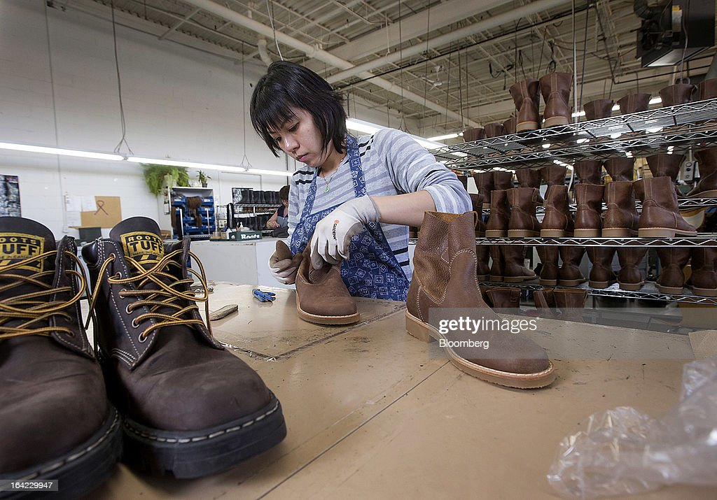 Employee Faye Ong does a final check on new boots at the Roots Ltd. manufacturing facility in Toronto, Ontario, Canada, on Wednesday, March 20, 2013. Roots Ltd., a Canadian clothing and lifestyle products retailer, manufactures footwear, leather goods, active athletic wear, yoga wear, accessories and home furnishings. Photographer: Norm Betts/Bloomberg via Getty Images