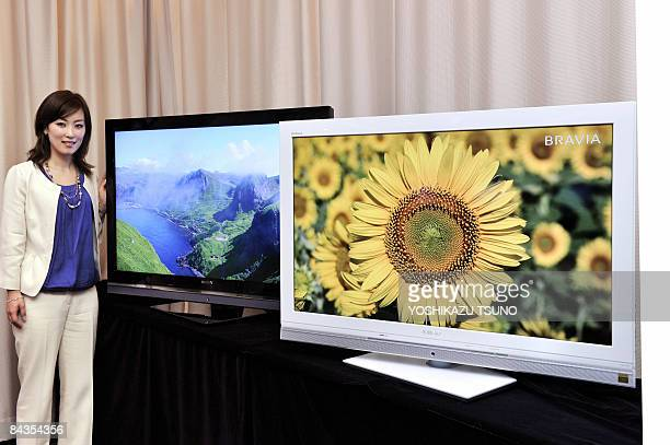 Employee for Japanese electronics giant Sony Emi Nagahara displays the company's new LCD TV 'Bravia V5 series' which reduces power consumption by...