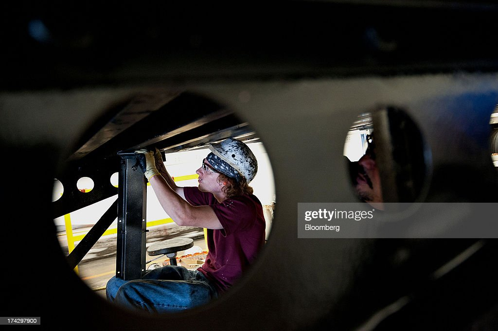 Employee Francis Wallers installs a support for a wind skirt beneath a semi trailer at the Wabash National Corp. facility in Lafayette, Indiana, U.S., on Monday, July 22, 2013. Wabash National Corp. is scheduled to release earnings figures on July 30. Photographer: Daniel Acker/Bloomberg via Getty Images