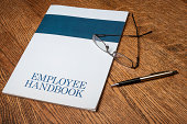 Employee handbook manual on a desktop with glasses and a mechanical pencil