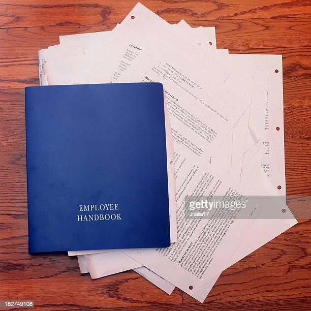Mitarbeiterhandbuch gefüllt mit Papierkram
