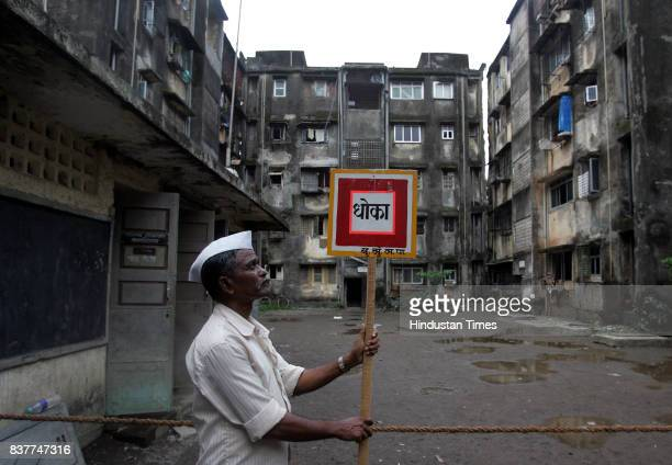 BMC employee holds a sign board signalling the residents about the buildings of Ratnadeep Cooperative Housing Society developing cracks