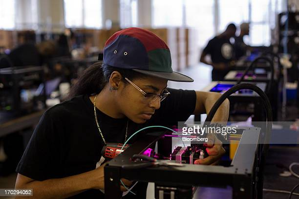 Employee Imanei Cedeno assembles a Makerbot Industries LLC 3D Printer at the company's new factory in the Brooklyn borough of New York US on Thursday...
