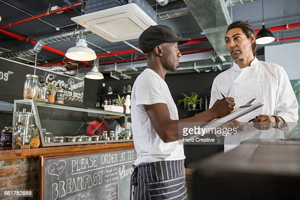 Employee in restaurant talking with chef, making notes on clipboard