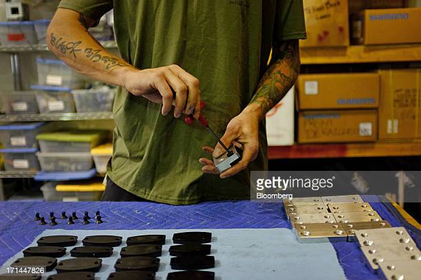Employee Jay Knight fits brake pads at the Main Street Pedicabs Inc manufacturing facility in Broomfield Colorado US on Monday June 24 2013 The US...