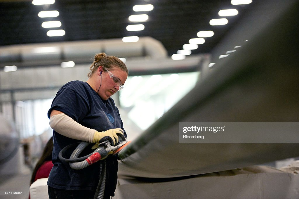 Employee Jennifer Gilkison uses a sander as she prepares a finished wind turbine blade made for General Electric Co.'s renewable energy business for paint at TPI Composites Inc.'s manufacturing facility in Newton, Iowa, U.S., on Friday, June 22, 2012. The U.S. Census Bureau is scheduled to release durable goods data on June 27. Photographer: Daniel Acker/Bloomberg via Getty Images