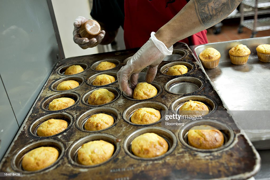 Employee Jimmie Ellington removes corn bread muffins from a cooking tray at a Famous Dave's of America Inc. franchise restaurant in Peoria, Illinois, U.S., on Thursday, March 21, 2013. Famous Dave's of America is a chain of barbecue restaurants started in 1994 that has 191 locations in 34 U.S. states and one Canadian province. Photographer: Daniel Acker/Bloomberg via Getty Images