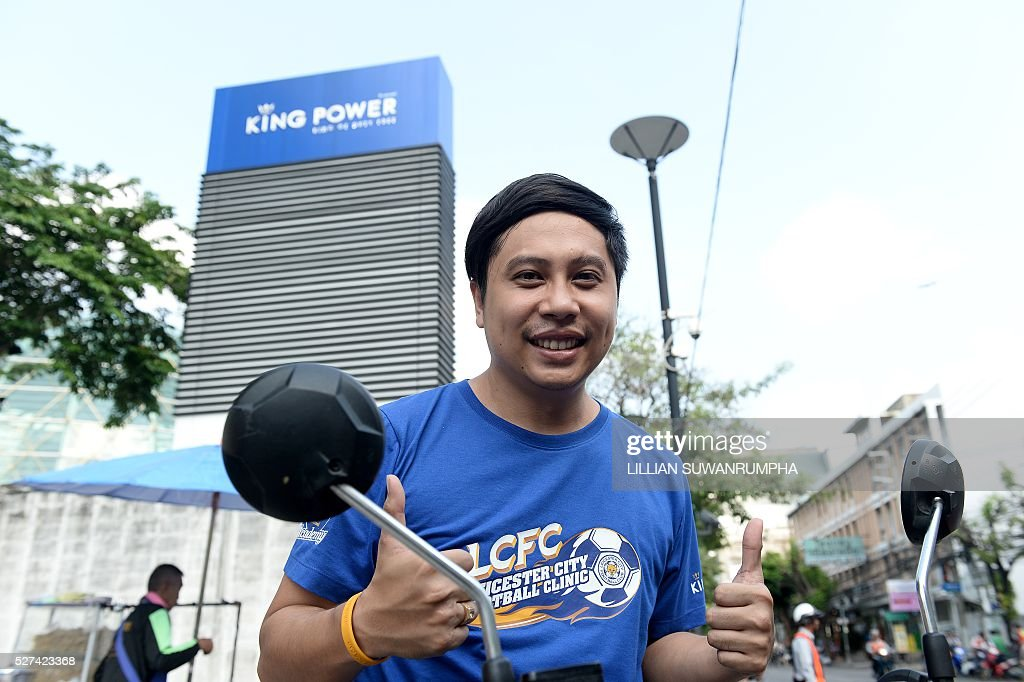 Employee Jiratha Pawadee, 33, gives a thumbs up outside the Bangkok headquarters of King Power, a company owned by Thai magnate Vichai Srivaddhanaprabha who also knowns English Premier League champions Leicester City, the morning after Leicester clinched the chamionship on May 3, 2016. The Foxes, virtual unknowns in Thailand until they were bought by duty-free magnate Vichai Srivaddhanaprabha in 2010, have seen their popularity snowball during the title run-in. Supporters at the downtown headquarters of Vichai's King Power firm spoke of their joy at the Thai link to a win in the Premier League which is assiduously watched in the kingdom. / AFP / LILLIAN