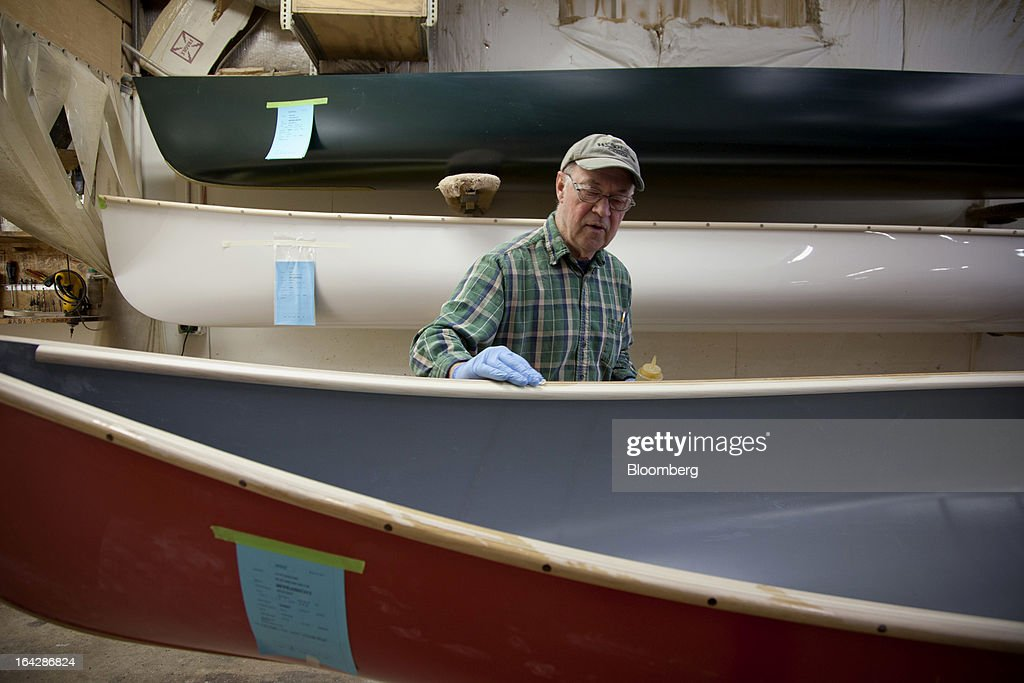 Employee Jon Hatleli uses tung oil on the gunwales of a Royalex canoe at the Wenonah Canoe factory in Winona, Minnesota, U.S., on Thursday, March 21, 2013. Wenonah Canoe, the second largest user of Kevlar fabric after the U.S. military, produces roughly 2500 canoes and 4000 kayaks each year. Photographer: Ariana Lindquist/Bloomberg via Getty Images