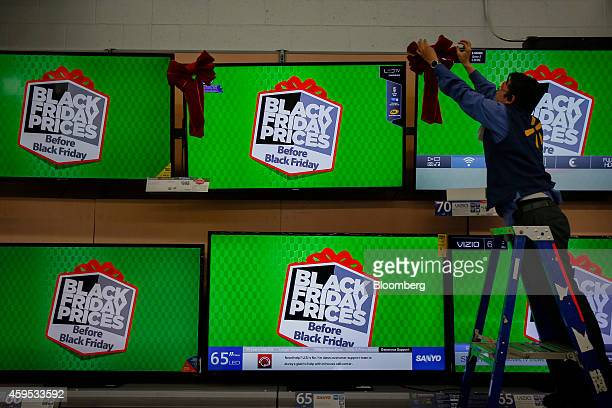 Employee Jonathan Dobravolskis fixes a bow on televisions displayed for sale at a WalMart Stores Inc location ahead of Black Friday in Los Angeles...