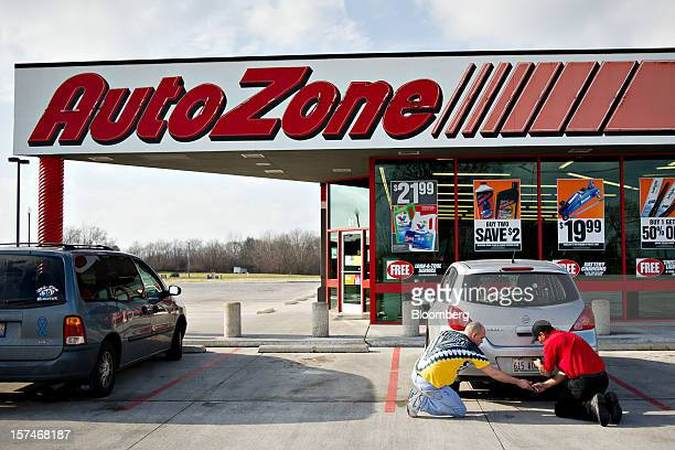 Employee Jonathan Splitt right helps a customer change a license plate bulb outside an AutoZone Inc store in Princeton Illinois US on Monday Dec 3...
