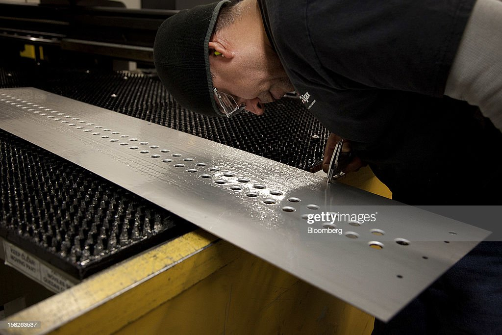 Employee Jose Chavarria, a former Marine Master Gunnery Sergeant, measures a product with a pair of calipers at the E.J. Ajax & Sons metalforming company in Minneapolis, Minnesota, U.S., on Thursday, Dec. 6, 2012. The U.S. Federal Reserve is scheduled to release industrial production data on Dec. 14. Photographer: Ariana Lindquist/Bloomberg via Getty Images