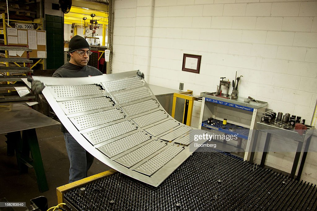 Employee Jose Chavarria, a former Marine Master Gunnery Sergeant, lifts a sheet of metal at the E.J. Ajax & Sons metalforming company in Minneapolis, Minnesota, U.S., on Thursday, Dec. 6, 2012. The U.S. Federal Reserve is scheduled to release industrial production data on Dec. 14. Photographer: Ariana Lindquist/Bloomberg via Getty Images