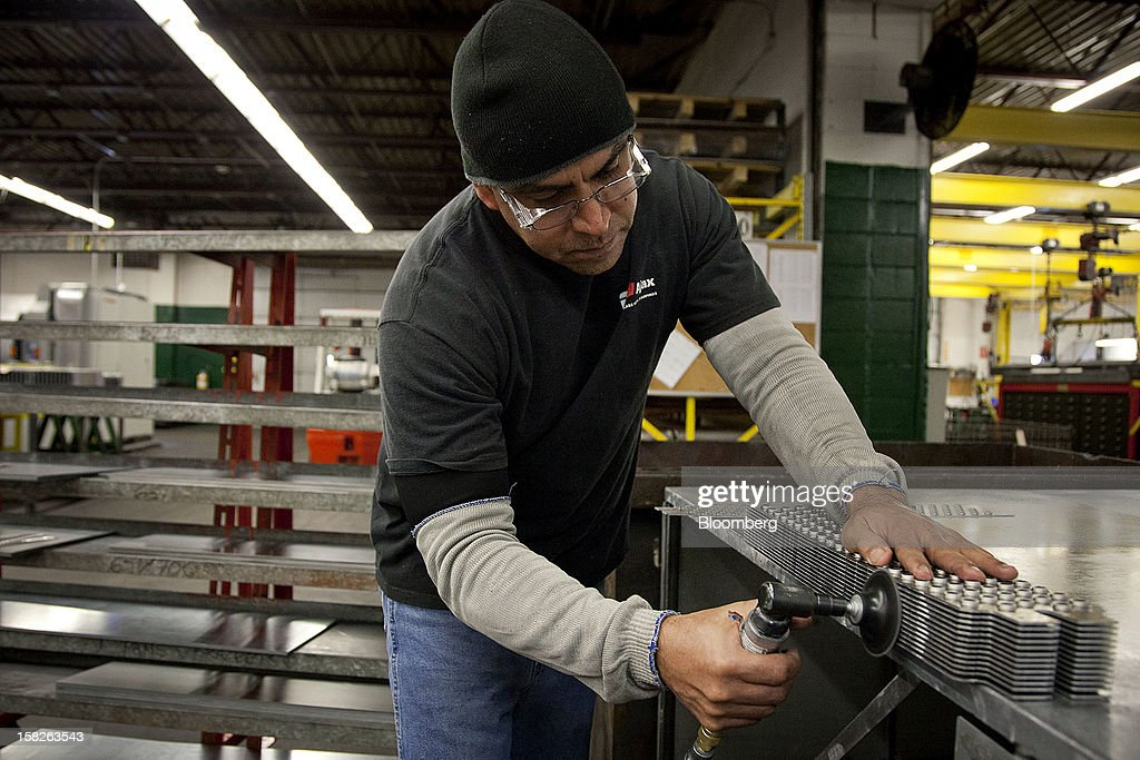 Employee Jose Chavarria, a former Marine Master Gunnery Sergeant, smooths the edges of metal plates at the E.J. Ajax & Sons metalforming company in Minneapolis, Minnesota, U.S., on Thursday, Dec. 6, 2012. The U.S. Federal Reserve is scheduled to release industrial production data on Dec. 14. Photographer: Ariana Lindquist/Bloomberg via Getty Images