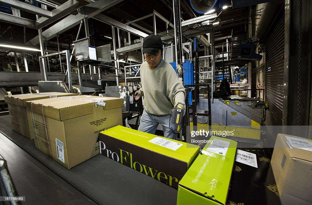 Employee Joseph Do scans packages unloaded from an air trailer at the United Parcel Service (UPS) distribution center in Sacramento, California, U.S., on Thursday, Feb. 14, 2013. 100 UPS delivery all-electric vehicles, developed by Electric Vehicles International (EVI), have been deployed this week and are said to eliminate the use of 126,000 gallons of fuel per year. Photographer: Ken James/Bloomberg via Getty Images