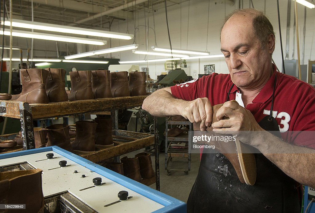 Employee Kahoren Barkhordarian glues a sole to the body of a boot at the Roots Ltd. manufacturing facility in Toronto, Ontario, Canada, on Wednesday, March 20, 2013. Roots Ltd., a Canadian clothing and lifestyle products retailer, manufactures footwear, leather goods, active athletic wear, yoga wear, accessories and home furnishings. Photographer: Norm Betts/Bloomberg via Getty Images