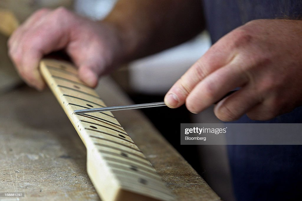 Employee Kevin Canton hand-files frets on the neck of a Lakland bass guitar at the company's production facility in Chicago, Illinois, U.S., on Thursday, Dec. 27, 2012. Manufacturing picked up in December, reflecting growth in orders, employment and exports that indicate the U.S. expansion will be sustained in 2013 following the budget deal. Photographer: Tim Boyle/Bloomberg via Getty Images