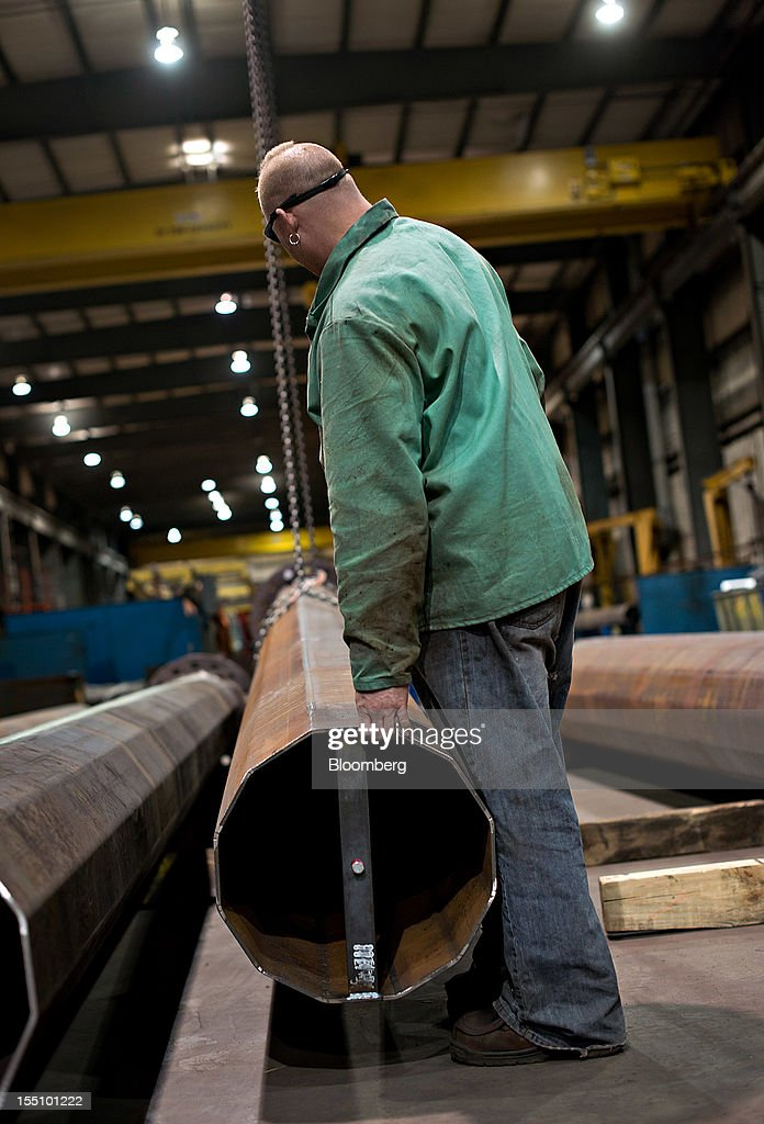 Employee Kevin Wertz lowers a section of a steel pole from an overhead crane at the Rohn Products LLC manufacturing facility in Peoria, Illinois, U.S., on Wednesday, Oct. 31, 2012. Manufacturing in the U.S. probably expanded in October at a slower pace, indicating the industry is providing little thrust for the expansion, economists said before a report today. Photographer: Daniel Acker/Bloomberg via Getty Images