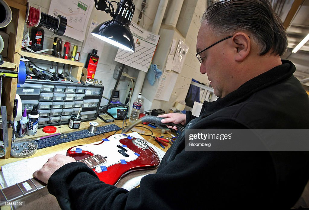 Employee Leo Lopez prepares to install electronics into a Lakland bass guitar at the company's production facility in Chicago, Illinois, U.S., on Thursday, Dec. 27, 2012. Manufacturing picked up in December, reflecting growth in orders, employment and exports that indicate the U.S. expansion will be sustained in 2013 following the budget deal. Photographer: Tim Boyle/Bloomberg via Getty Images