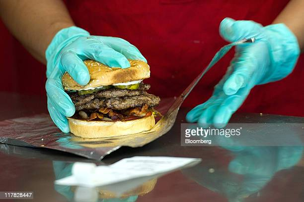 Employee Lilia Munguia wraps a cheese burger at a Five Guys Inc restaurant in Dublin California US on Wednesday June 29 2011 As twentysomethings...