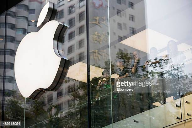 Employee look out while standing next to an Apple Inc logo displayed at the company's store during the sales launch of the iPhone 6s and iPhone 6s...