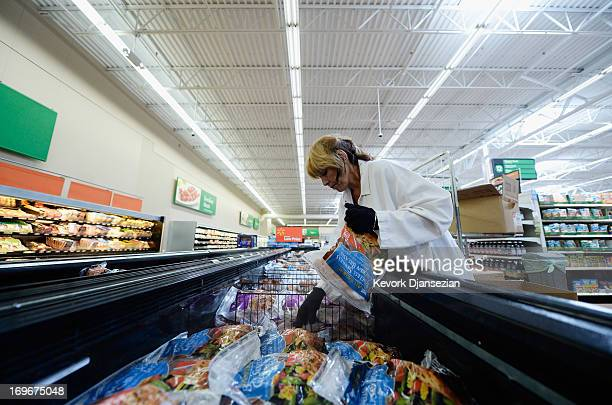 Employee Lucy Rodriguez stocks the frozen meat section of a Walmart Supercenter store on May 30 2013 in Pico Rivera California Walmart is the largest...