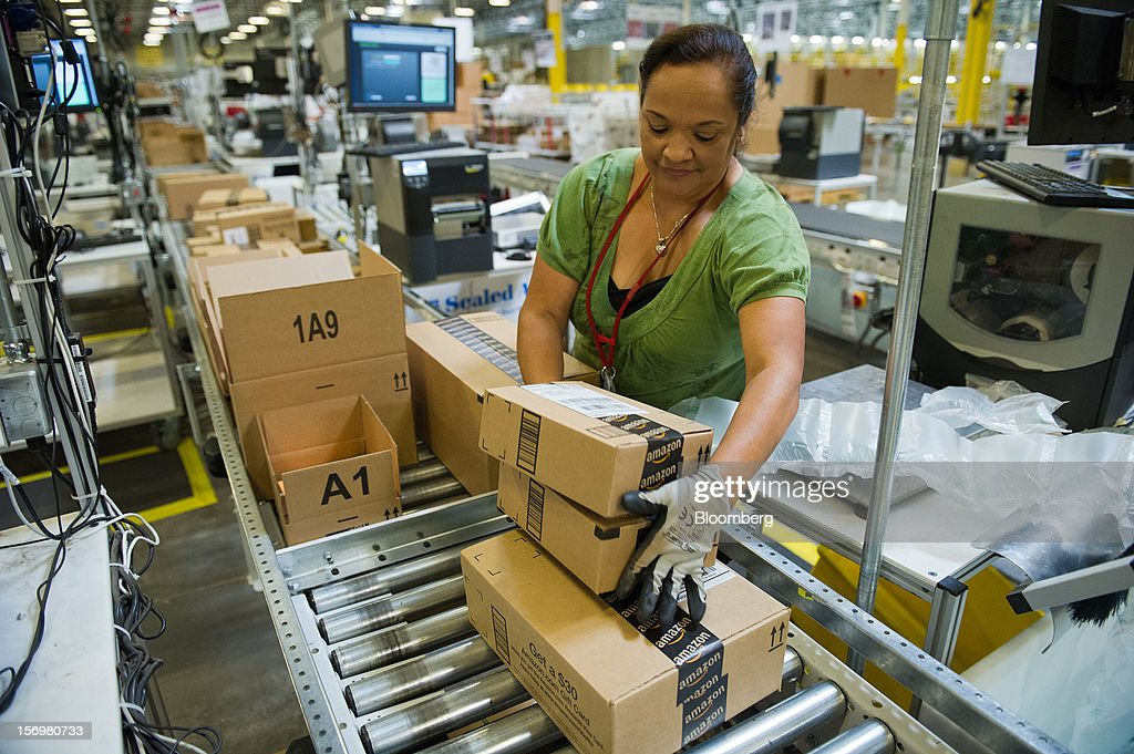 Employee Maria Miller loads boxes onto a conveyer belt for shipping at the Amazon.com Inc. distribution center in Phoenix, Arizona, U.S. on Monday, Nov. 26, 2012. U.S. retailers are extending deals into Cyber Monday and beyond to try to sustain a 13 percent gain in Thanksgiving weekend sales. Photographer: David Paul Morris/Bloomberg via Getty Images