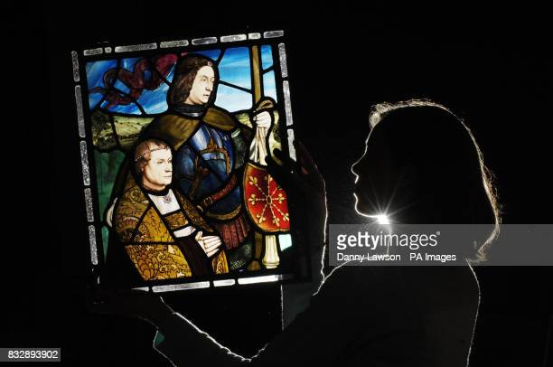 Employee Moira Gow holds a stain glass window at Lyon and Turnbull auctioneers in Edinburgh