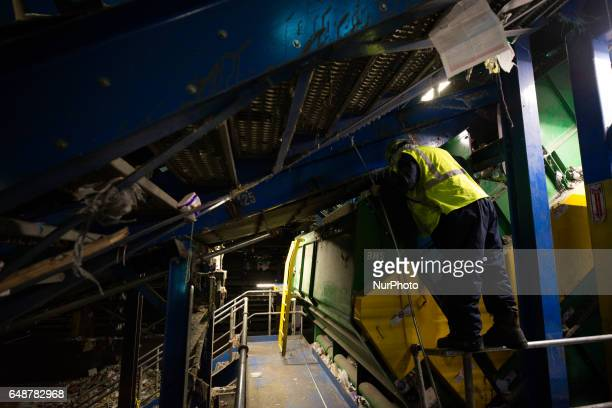 Employee monitors a section of the production as multiple layers of conveyer belts transport sorted and unsorted materials during the recyclables...