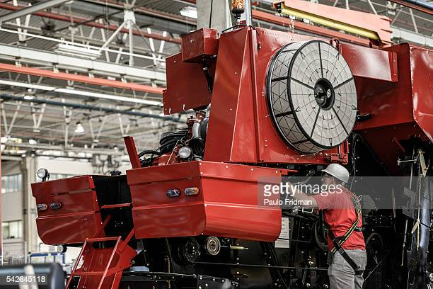 Employee mounts a grain combine At CASE Combines assembly line Sorocaba Brazil on Wednesday September 18th 2013