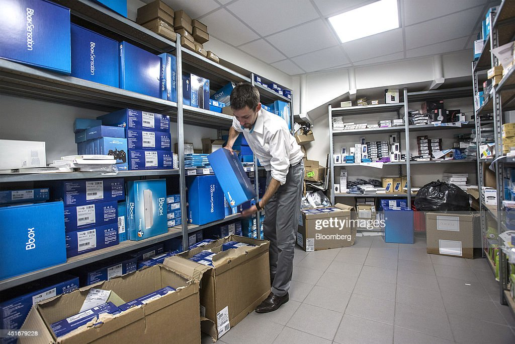 A employee moves boxes of the BBOX Sensation, a multimedia set top box from Bouygues Telecom, inside a store room at the company's mobile store, operated by Bouygues SA in Paris, France, on Thursday, July 3, 2014. Bouygues Telecom, France's third-largest mobile operator, was looking for a buyer as profitability and cash generation declined. Photographer: Balint Porneczi/Bloomberg via Getty Images