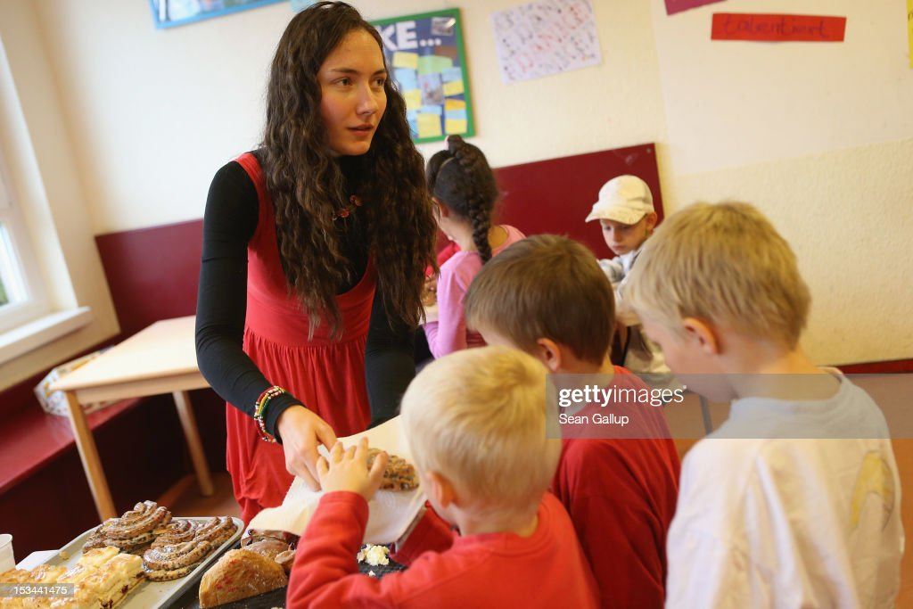 Employee Natalia Beck passes out sweet pastries to children at the 'Arche' youth center in Marzahn-Hellersdorf district on October 5, 2012 in Berlin, Germany. The Arche (which means Ark) is a Christian-based facility that provides children of all ages with a hot lunch, help with homework, arts and play facilities and in general a welcome place to come to in Marzahn-Hellersdorf district in east Berlin, a district with high levels of unemployment and social problems. An employee said up to 90% of the children come from challenged families and that many arrive at Arche illiterate.
