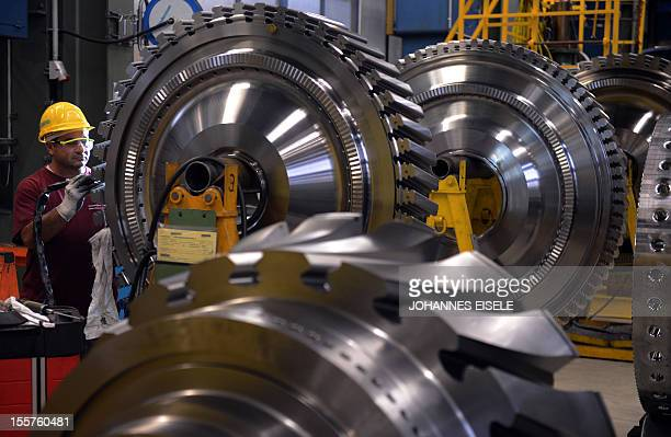 A employee of German industrial giant Siemens works on a rotor as a part of a Gas Turbine in the turbine plant on November 8 2012 in Berlin Siemens...