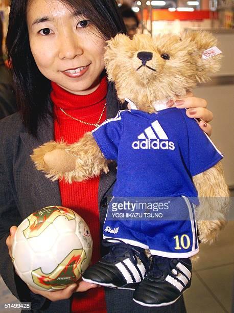 Employee of Japanese toymaker Takara Kumiko Endo displays a 37cm tall teddy bear produced by German teddy bear maker Steiff dressed in a soccer...