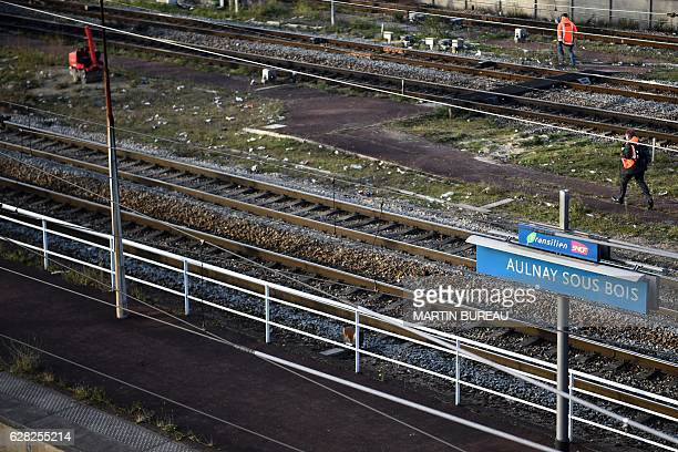 Employee of the SNCF railway company work on railways tracks of the station platform of AulnaysousBois near Paris on December 7 2016 after the...