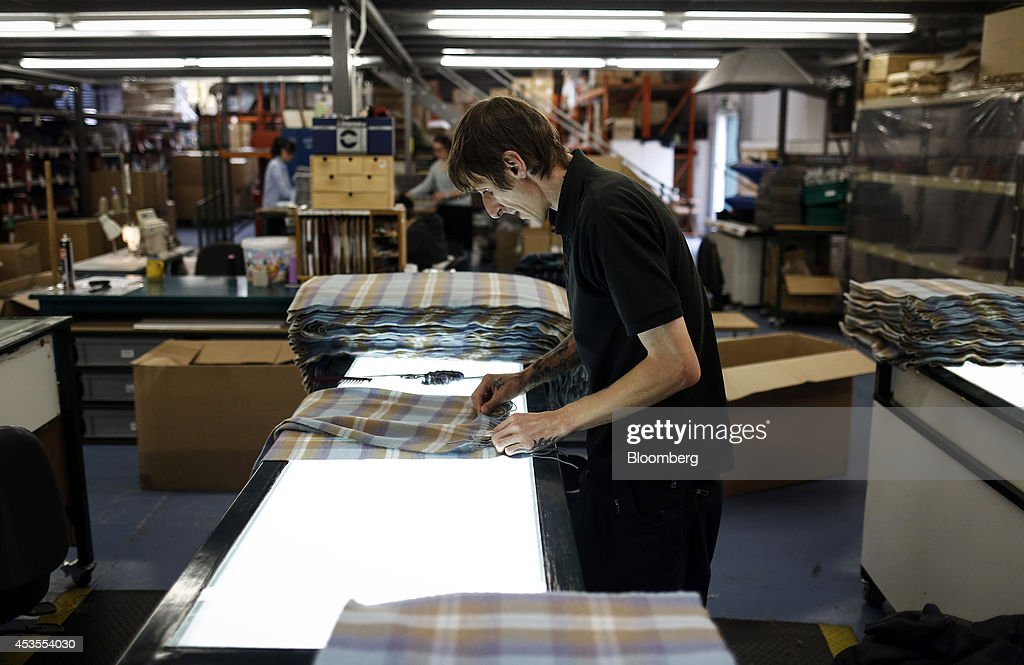 A employee quality control checks tartan scarves following completion at Lochcarron John Buchan Ltd.'s production plant in Selkirk, U.K., on Tuesday, Aug. 12, 2014. Scottish nationalists seeking independence from the U.K. lost ground in the latest poll of voting intentions for the Sept. 18 referendum, as campaigners to keep the 307-year-old U.K. intact extended their lead. Photographer: Simon Dawson/Bloomberg via Getty Images