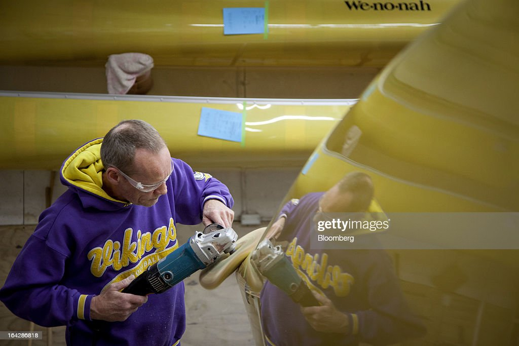Employee Ray Hill buffs the hull of a canoe at the Wenonah Canoe factory in Winona, Minnesota, U.S., on Thursday, March 21, 2013. Wenonah Canoe, the second largest user of Kevlar fabric after the U.S. military, produces roughly 2500 canoes and 4000 kayaks each year. Photographer: Ariana Lindquist/Bloomberg via Getty Images