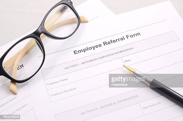 Employee referral form with a pen and glasses on a desk
