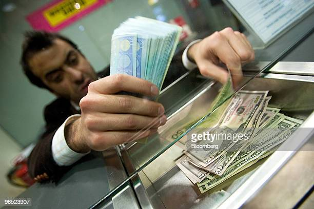 Employee Ricardo Lobo counts euros and US dollar notes in a currency exchange store in Lisbon Portugal on Tuesday Feb 9 2010 Portugal's credit rating...