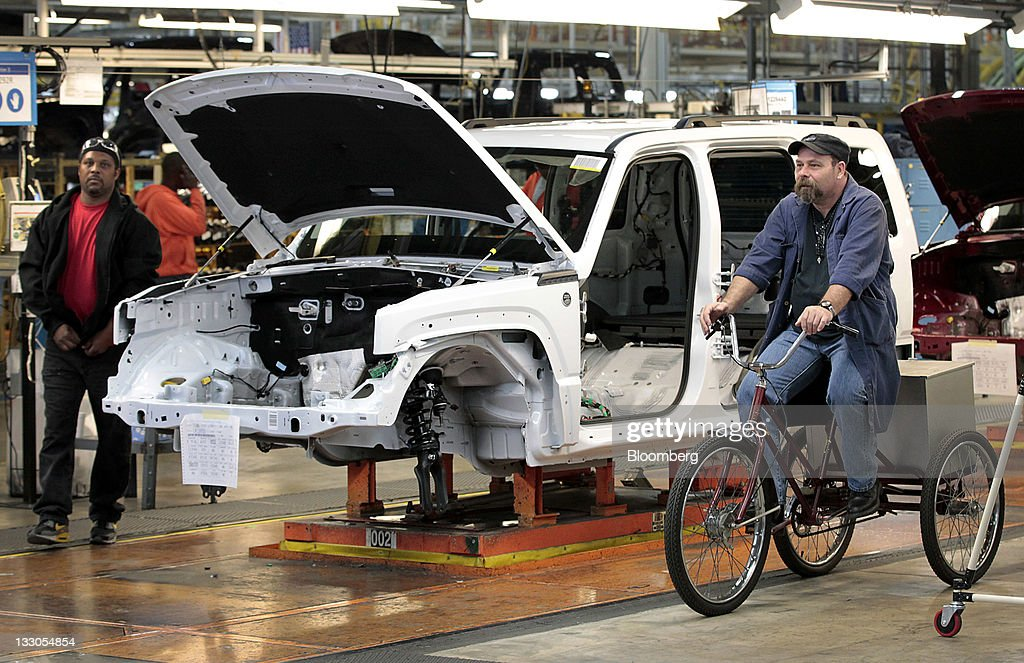 Employee Richard Klatt, right, rides a tricycle past a Jeep Liberty vehicle on the production line at Chrysler's Toledo Assembly Complex in Toledo, Ohio, U.S., on Wednesday, Nov. 16, 2011. Chrysler Group LLC said it will invest $1.7 billion to update a Jeep sport-utility vehicle and add a second shift at its factory in Toledo in the third quarter of 2013. Photographer: Jeff Kowalsky/Bloomberg via Getty Images