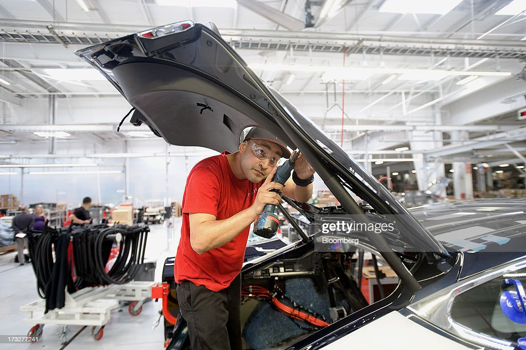Employee Robert Rodriguez installs interior trim on a Telsa Motor Inc. Model S sedan at the company's assembly plant in Fremont, California, U.S., on Wednesday, July 10, 2013. Tesla, is building Model S electric sedans faster than its initial 400-a-week goal as demand and the companys production skills increase, Chief Executive Officer Elon Musk said. Photographer: Noah Berger/Bloomberg via Getty Images