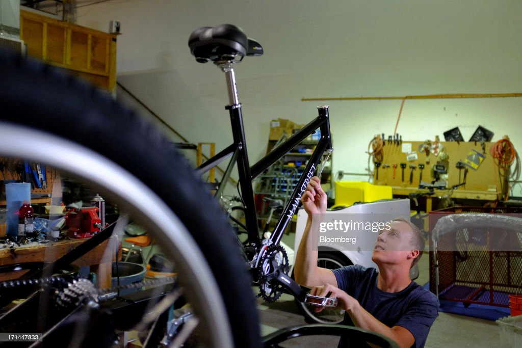 Employee Ryan McKelvey installs components to the frame of a pedicab at the Main Street Pedicabs Inc. manufacturing facility in Broomfield, Colorado, U.S., on Monday, June 24, 2013. The U.S. Census Bureau is scheduled to release durable goods figures on June 25. Photographer: Matthew Staver/Bloomberg via Getty Images