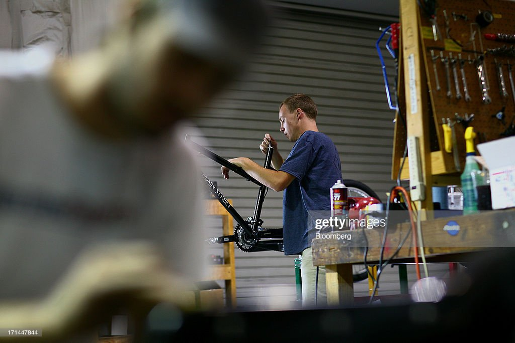 Employee Ryan McKelvey, right, installs components to the frame of a pedicab at the Main Street Pedicabs Inc. manufacturing facility in Broomfield, Colorado, U.S., on Monday, June 24, 2013. The U.S. Census Bureau is scheduled to release durable goods figures on June 25. Photographer: Matthew Staver/Bloomberg via Getty Images