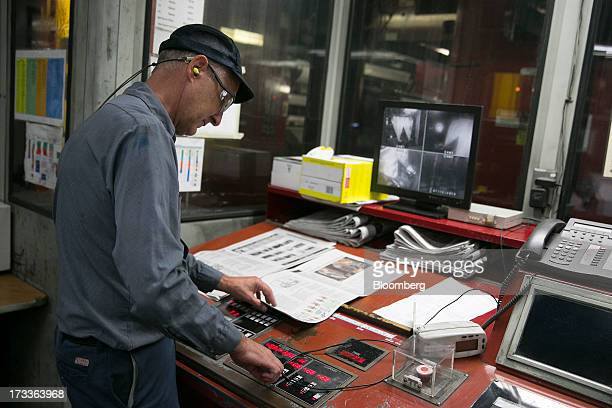 Employee Sam Dorick inputs data after checking ink density of a newspaper in the control room of the Washington Post newspaper production facility in...