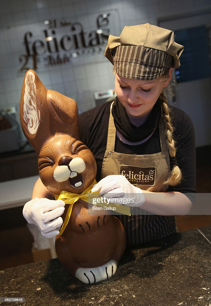Employee Sandra Jaeckel, at the photographer's request, adjusts a ribbon around the neck of a giant chocolate Easter bunny at the production facility at Confiserie Felicitas chocolates maker on April 9, 2014 in Hornow, Germany. Easter is among the busiest times of year for the chocolatier, which produces Easter bunnies and eggs in a wide variety of sizes and styles. Founded by Belgian expats Goedele Matthyssen and Peter Bientsman the company will soon celebrate its 21st year.
