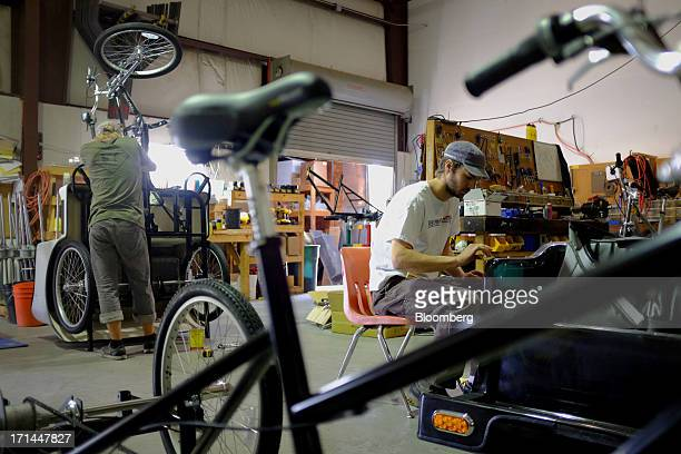 Employee Sean Gore right works on a fiberglass carriage at the Main Street Pedicabs Inc manufacturing facility in Broomfield Colorado US on Monday...